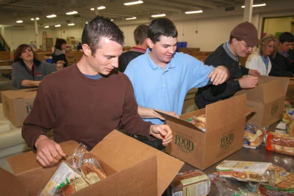 OKFB employees putting packaged food into boxes for donation