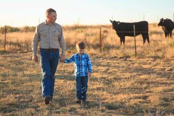 rancher and young son look at cattle