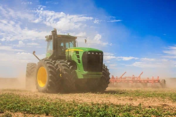 large green tractor harvesting crops