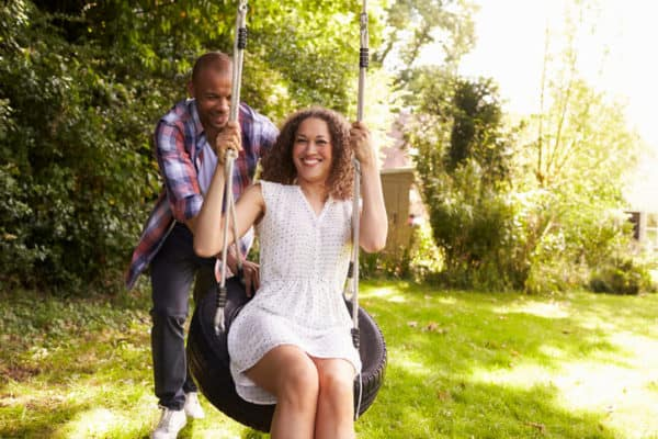 man pushes woman on tire swing in back yard of rental property