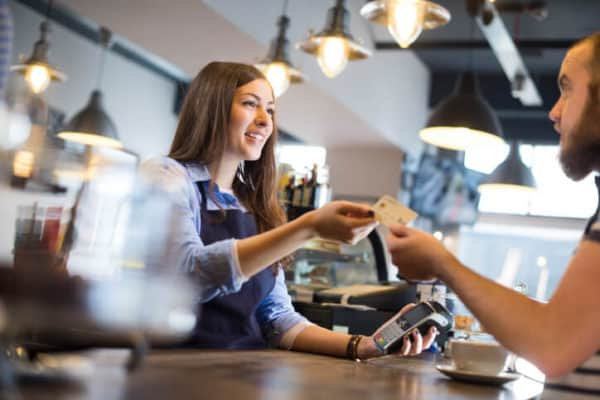female barista employee taking payment for a coffee