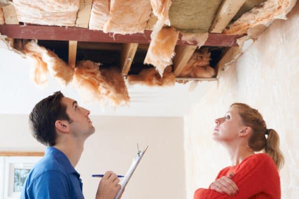 woman speaking with claims adjuster about damaged roof