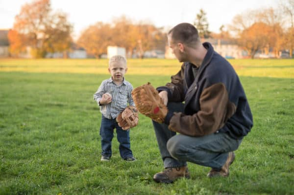 father teaches his young son how to play baseball