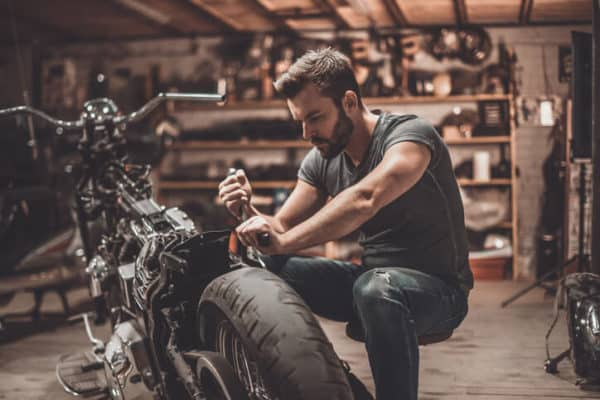 man working on his motorcycle in a shop