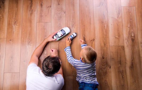 father plays with toy cars with his son on the hardwood floor of mobile home