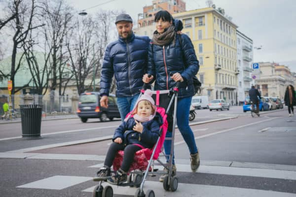 young family takes a walk in the city with child in pink stroller