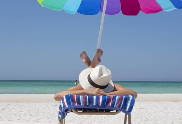 Woman relaxing on beach in beach chair with umbrella.