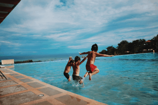 Children jumping into swimming pool on hot summer day