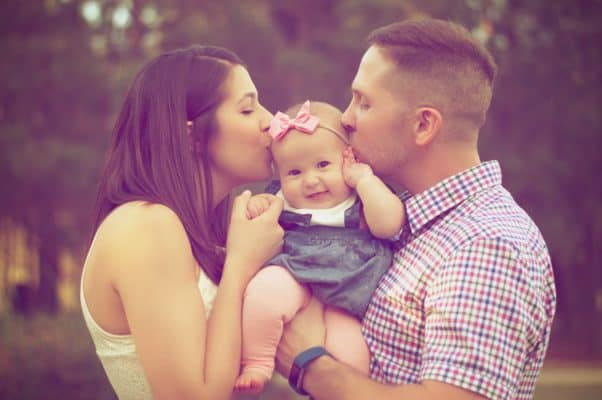 Parents hold their young child and kiss her on the head.