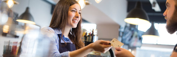 Cashier smiling and completing transaction