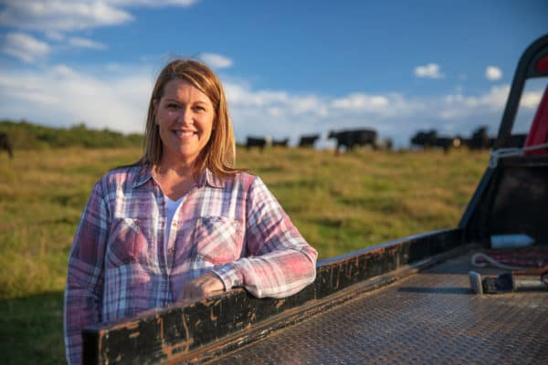 woman farmer standing outside next to pickup truck