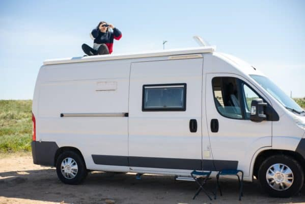 woman sitting on top of motorhome that has recreational insurance
