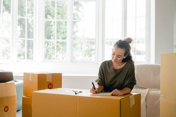 woman thinking about renters insurance as she packs