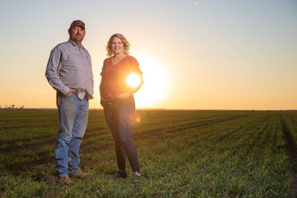 woman and man standing on their farm thinking about their farm transition plan