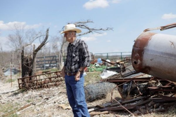 Carl looking at the damage done to his farm because of a tornado