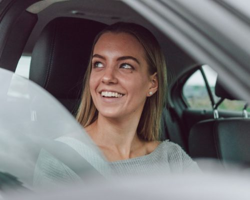 young girl smiling in her car because she has auto insurance