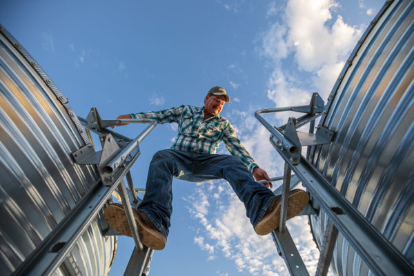 farmer standing between two grain bins after reviewing farm apps